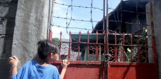 FIRE VICTIMS. A young resident peeks behind the metal gate of Tourism assistant secretary Eden Josephine David's house which was gutted by fire early morning of Saturday. David's nine-year old son and a house help died while the assistant secretary and a house boy were injured during the incident. Lean Daval Jr.