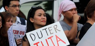 NTI-DUTERTE PLACARD. A protester holds a placard written with ͞DUTER TUTA͟ during the national day of unity and rage against the Marcos burial at the Libingan ng mga Bayani rally at the Freedom Park along Roxas Avenue in Davao City on Friday evening. Lean Daval Jr.