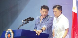 """BONUS. President Rodrigo Duterte listens to Presidential Management Staff head Christopher """"Bong"""" Go as they confer before announcing that he will give cash gifts to Barangay officials during the Christmas party held at the Davao City Recreation Center on Tuesday evening. Barangay captains received P10,000 each while barangay councilors got P3,000 each. Duterte bared that the money came from a politician's donation for his electoral campaign which he did not use. LEAN DAVAL JR."""