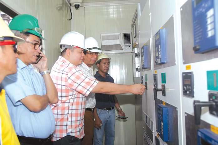 POWER BOOST. Davao Light and Power Company executive vice president and chief operating officer (EVP and COO) Arturo Milan (leftmost), incoming EVP and COO Engr. Rodger Velasco (second from right) and Substation and Electrical Equipment Department (SEED) manager Engr. Ledio Peñafiel (rightmost) assist Mayor Al David Uy of Island Garden City of Samal (IGaCoS) as he turns on the switch to energize and reconnect the Samal submarine cable at DLPC Pampanga substation in Bo. Pampanga, Davao City yesterday. Uy requested DLPC to provide stable electricity to Samal as the generator sets currently supplying electricity is not sufficient to energize the entire island. LEAN DAVAL JR.