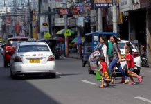 JAYWALKING. Two mothers and their children cross San Pedro Street a few meters away from a pedestrian lane yesterday. Some Dabawenyos still violate the city's Anti-Jaywalking Ordinance a week after its implementation. LEAN DAVAL JR.