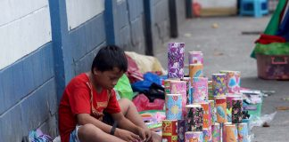 ALL IN A DAY. A young street vendor counts his earnings from selling Christmas-designed piggy banks and slippers along the sidewalk in San Pedro Street, Davao City yesterday. LEAN DAVAL JR.