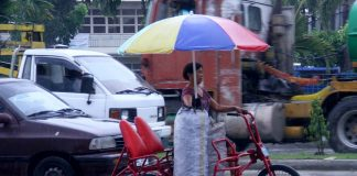 """NEVER SAY NEVER. A woman drives a """"trisikad"""" as she braves the heavy downpour to buy charcoal which she will be using for her banana cue business along R. Castillo Street in Davao City yesterday. LEAN DAVAL JR."""