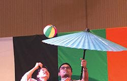 Daikagura Lucky Mai shows a volunteer how to juggle a ball on an umbrella