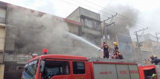 DAVAO FIRE. Firefighters try to put out a fire at the junction of Lizada St. and Ramon Magsaysay Ave. in Davao City Tuesday (21 Feb 2017). Firemen said the blaze began at 4 a.m. at a boarding house behind the building where a cellphone charger was left unattended. By noon, or over six hours later, the firemen were still hosing down an establishment in the building selling helmets and motorcycle tires. (MindaNews photo by Gigi Bueno)