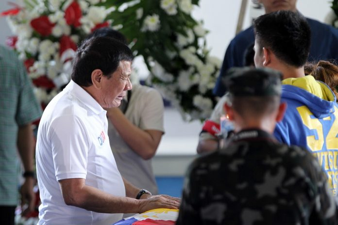 SHARING THE PAIN. President Rodrigo Duterte reacts while looking at the remains of Corporal Michael Yadao at Naval Station Felix Apolinario in Panacan, Davao City on Friday afternoon. Duterte visited the wake of Yadao and Private Virnel Damondon who were both killed in an encounter with the New People's Army at the Brgy. Lamanan, Calinan District, Davao City on Thursday. LEAN DAVAL JR.