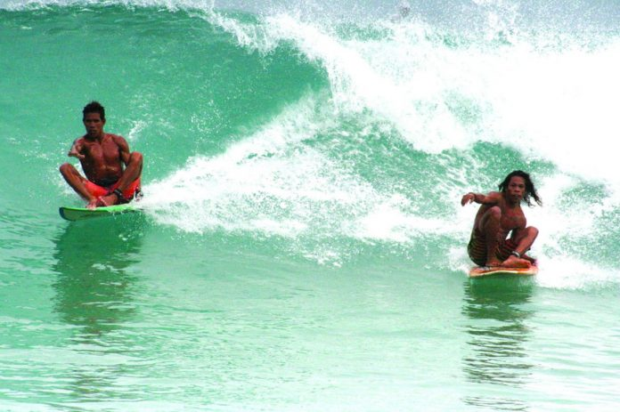 "Locals just wanna have fun. Champion skimboarder Sonnyboy ""Bayogyog"" Aporbo (left) and Michael ""Daggy"" Bucong share a wave seated on their surf boards."