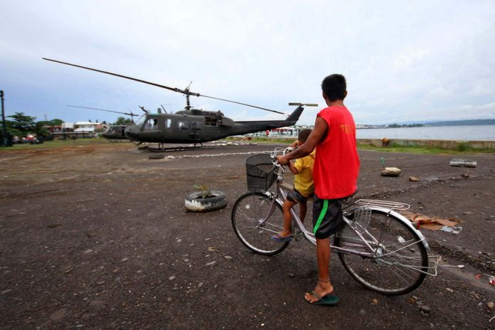 FIRST-HAND VIEW. A father and his young son watch as government choppers land at Sta. Ana Port yesterday for today's simulated exercise to test their capability and preparedness of Task Force Haribon's component units. LEAN DAVAL JR.