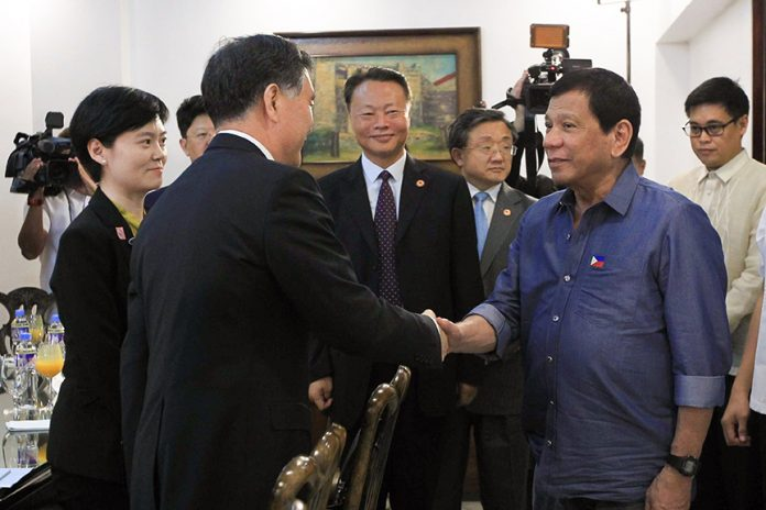 President Rodrigo Roa Duterte greets Vice-Premier of the State Council of the People's Republic of China Wang Yang who paid a courtesy call on the President at the Presidential Guest House in Davao City on March 17, 2017. Also in the photo is Chinese Ambassador to the Philippines Zhao Jianhua. ACE MORANDANTE/Presidential Photo