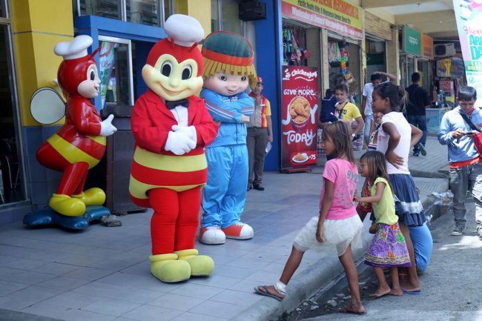 AMUSED. Badjao children watch in amusement as mascots of a popular food chain perform their dance routine along R. Magsaysay Avenue in Davao City yesterday. LEAN DAVAL JR.