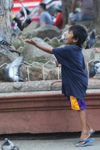 WISH FULFILLED. A young boy appears to be very amused after feeding a pigeon with bird seeds from his palm at the Rizal Park in Davao City on Thursday. LEAN DAVAL JR.