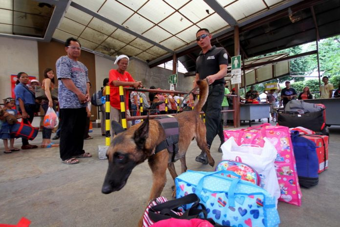 TIGHT SECURITY. A personnel of Task Force Davao and his bomb sniffing dog inspect the belongings of province-bound passengers at the entrance of the Davao City Overland Transport Terminal (DCOTT) on Tuesday. LEAN DAVAL JR.