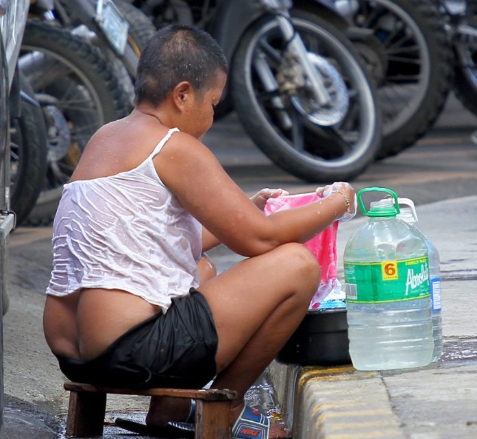 DOUBLE TIME. A street vendor does her laundry at the sidewalk near Davao City Hall at the same time vend as she needs to earn money for her family while attending to some chores that she's supposedly doing at home. LEAN DAVAL JR.