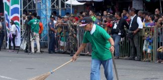 TIDYING UP. A worker from the City Environment and Natural Resources Office (Cenro) cleans up the thrash left by revelers during yesterday's 80th Araw ng Davao Parada Dabawenyo. LEAN DAVAL JR.