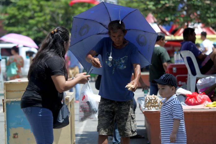AT HAND. vendor sells packs of bird seeds to park-goers who want to feed and take photos with the popular pigeons at Rizal Park in Davao City yesterday. LEAN DAVAL JR.
