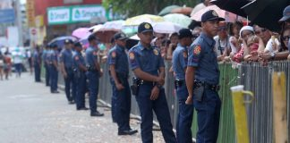 EVER WATCHFUL. Police personnel stand guard in front of the spectators as part of the tighter security measures being implemented during yesterday's 80th Araw ng Davao Parada Dabawenyo. LEAN DAVAL JR.