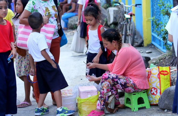 FAVORITE. Elementary students buy tamarind candies from a vendor outside Magallanes Elementary School in Davao City yesterday. LEAN DAVAL JR.
