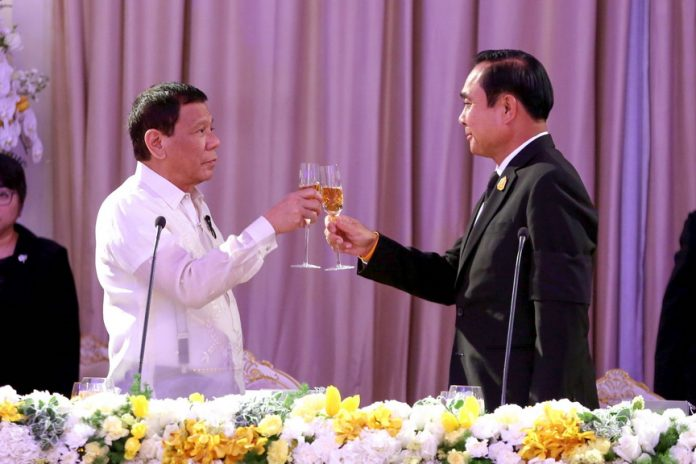 HONORING THE OCCASION. President Rodrigo Duterte and Thai Prime Minister General Prayut Chan-o-cha hold a toast during the state dinner at the Government House in Bangkok, Thailand on Wednesday night. RICHARD MADELO/Presidential Photo