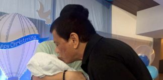 """PROUD LOLO. President Duterte kisses his """"apo"""", Stonefish, after his baptism on Thursday, March 16 at the St. Francis Assisi Church in Maa. (CIO Photo)"""