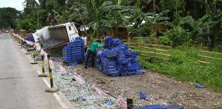 Workers pile softdrink cases on Monday (24 April 2017), three days after the hauler truck rammed motorbike riders killing three of them in Barangay Malasila, Makilala, North Cotabato. Mindanews Photo