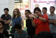 THRILLED. Davao City Tourism Office head Generose Tecson takes photos of the paintings created by Mindanao artists during Dabawenya alla Prima of Visit Davao Fun Sale's (VDFS) Art Mindanao held at Abreeza mall on Friday afternoon. LEAN DAVAL JR