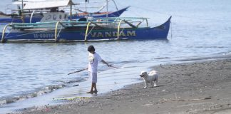 FAR FROM THE CROWD. A dog owner and her pet enjoy a quiet morning stroll along the beachfront of Times Beach in Ecoland, Davao City on Wednesday, a few days after the Holy Week celebration when thousands of Dabawenyos troop to the city's beaches. LEAN DAVAL JR.