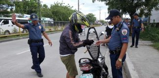 ROUTINE CHECK. A police personnel from Sta. Ana Police Station inspects a rider's license at a checkpoint along R. Castillo Street in Davao City on Good Friday as part of a tighter security measures being implemented by authorities in the city during the Holy Week. LEAN DAVAL JR.