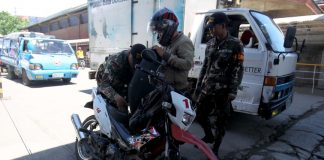 MOTOR FRISK. Task Force Davao personnel thoroughly inspect a motorcycle of an Island Garden City of Samal (IGaCoS) bound rider at the entrance of Sasa Ferry Wharf in Km. 11, Sasa, Davao City on Saturday. LEAN DAVAL JR.