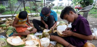 MAKING DO. Teenagers spend their summer break working as coconut meat scraper at a makeshift store selling fresh 'buko' juice and meat along Jacinto Extension in Davao City, a popular stopover for thirsty public utility vehicle drivers. LEAN DAVAL JR.