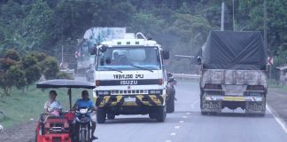 UNCONCERNED. A 'payong-payong' driver seems to be ignoring the danger of being hit by large vehicles as he traverses his unregistered vehicle with passengers in tow along the Davao-Cotabato national highway on Monday. LEAN DAVAL JR.
