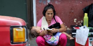 TWO-IN-ONE.A street vendor cuddles a young girl who is sleeping soundly as she computes the day's earnings of her makeshift stall along Magallanes Avenue in Davao City on Thursday. LEAN DAVAL JR.