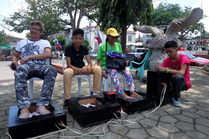 FOR A CHANGE. Park goers try out electronic foot massager for P25 per 26 minute-session at Rizal Park in Davao City on Thursday. LEAN DAVAL JR.