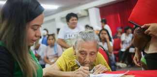 """MONETARY REPARATION. Mamerta Osorio, already in her 80s, receives monetary reparation from the Human Rights Victims' Claims Board in Davao City on Saturday (13 May 2017) for her late husband Amando, a human rights abuse victim under Martial Law. Members of the Philippine Constabulary illegally arrested and detained Amando, a farmer, in 1981 on charges that he was a rebel. While in detention, government agents burned down their house in Mudiang, Tibungco, Davao City. Amando's brothers Ebilio and Margarito were """"salvaged"""" (summarily executed) in the public cemetery of Tibungco during Martial Law. MindaNews photo by Manman Dejeto"""