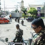 Army troops in an armored personnel carrier stand guard in one of the streets in downtown Cotabato City Wednesday (24 May 2017) as residents pass just like normal times. President Rodrigo Duterte declared martial law in Mindanao late evening Tuesday hours after members of the Maute Group terrorized Marawi City. MindaNews photo by Ferdinandh Cabrera