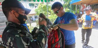 A member of Task Force Davao performs a search on a bus passenger's backpack at a checkpoint in Lasang, Davao City on Wednesday (24 May 2014) as the city tightens security following the declaration of martial law for the whole of Mindanao by President Rodrigo Duterte. MindaNews photo by Manman Dejeto