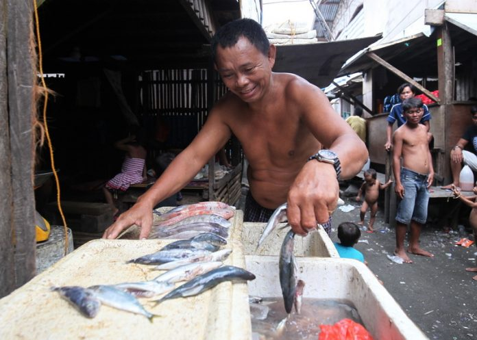 WHATEVER IT TAKES. A villager displays different varieties of fish he is selling at his community in Brgy. 23-C, Isla Verde, Davao City on Thursday. LEAN DAVAL JR