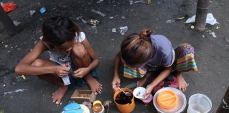 ENTERPRISING.Two Badjao girls prepare the sauce for the fish crackers they are selling at their community in Brgy. 23-C, Isla Verde, Davao City on Monday. LEAN DAVAL JR.