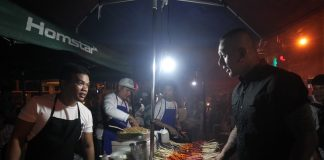 NO LET-UP. A street food vendor entertains a customer at a makeshift stall at Roxas night market in Davao City on Wednesday evening. Dabawenyos continue to flock to their favorite food stalls in the city's night market a day after President Duterte declared martial law. LEAN DAVAL JR