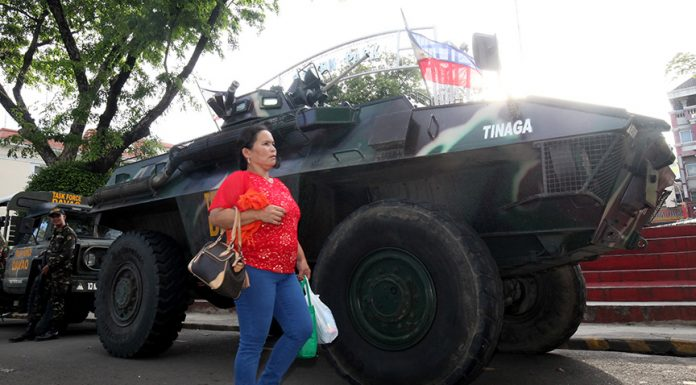 ADDED FIREPOWER. A resident walks by a light armor vehicle of Task Force Davao stationed in front of the Davao City Hall after Mayor Sara Duterte-Carpio ordered to lockdown the city following the declaration of President Duterte that the entire Island of Mindanao is under martial law due to the terror attacks in Marawi City. LEAN DAVAL JR.