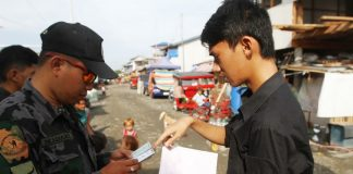 """OPLAN BOLABOG. A police officer checks the identification card of a student during the """"Oplan Bolabog"""" at Isla Verde in Davao City Thursday morning (25 May 2017). The operation was meant to verify non-residents as part of the city's tightened security measures. Mindanews photo"""
