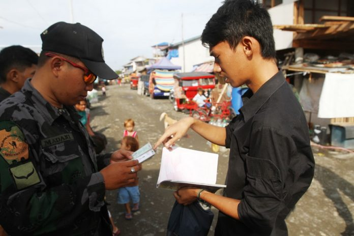 OPLAN BOLABOG. A police officer checks the identification card of a student during the