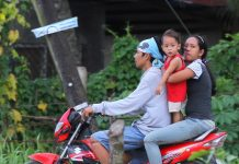 RISKY RIDING. A young boy is being held by his mother while riding a motorcycle in Panabo City on Thursday. Republic Act 10666 or the Children's Safety on Motorcycles Act which prohibits small children from riding motorcycles along national roads and highways nationwide takes effect starting today. LEAN DAVAL JR.
