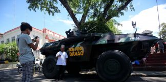 PHOTO OPPORTUNITY. A Muslim resident has his photograph taken with Task Force Davao's light armor vehicle parked in front of the City Hall of Davao on Saturday. The Muslim community in Davao City, which celebrated the start of Ramadan Saturday morning, has no opposition on the martial law declared by President Duterte. LEAN DAVAL JR.