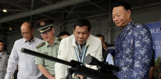 President Rodrigo Roa Duterte examines one of the firearms donated by the People's Republic of China (PRC) during the ceremonial turnover of the military assistance gratis at the Clark Air Base in Pampanga on June 28, 2017. Joining the President are Defense Secretary Delfin Lorenzana, PRC Military and Defense Attache Wang Xianyun and Chinese Ambassador to the Philippines Zhao Jianhua. RICHARD MADELO/PRESIDENTIAL PHOTO