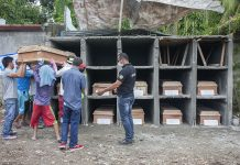 Cemetery workers place the last of the 11 coffins containing the bodies of still unidentified victims in the Marawi City siege in their final resting place at the cemetery in Barangay Dalipuga, Iligan City. The interment was attended mainly by local government employees and the media. MindaNews photo by Bobby Timonera