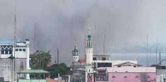 """NOT BOMBED. The Bato Ali mosque located within the conflict zone in Marawi City stands against a backdrop of smoke from bombs dropped at a distance on Wednesday (14 June 2017). The Armed Forces of the Philippines has issued a statement categorically stating that it has """"not bombed and will not bomb mosques in Marawi."""" The Maute terror group has reportedly encamped in mosques and uses them as machine-gun and snipers' nests. MindaNews photo by Froilan Gallardo"""