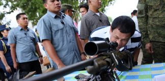 President Rodrigo Roa Duterte looks through the scope of a sniper rifle as he led the inspection of firearms recovered by the troops of the 4th Infantry Division upon his visit at the 4th Infantry Division Advance command Post in Butuan City on June 17, 2017. ROBINSON NIÑAL JR./PRESIDENTIAL PHOTO