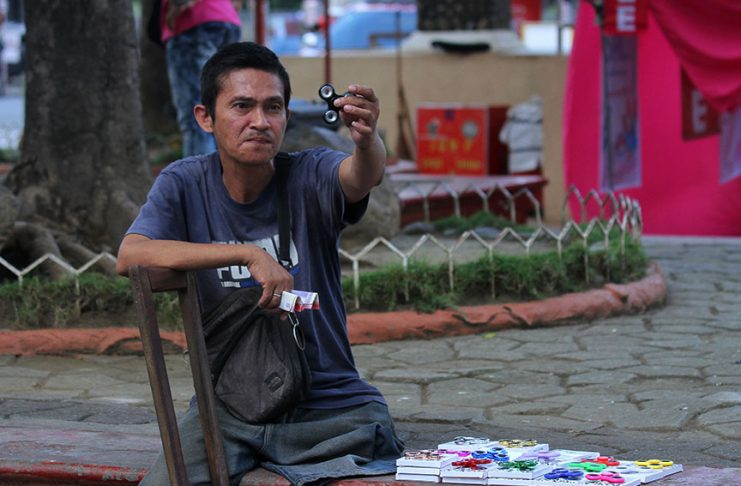 TO EACH HIS OWN GIMMICK.A physically impaired sidewalk vendor shows off his spinner ring skills to entice passersby to purchase the fidget spinners he is selling at Rizal Park in Davao City on Wednesday. Fidget spinner became popular toy among kids and teenagers but a recent report surfaced that its main purpose is to assist ADHD patients and mentally disturbed people fight mild anxiety. LEAN DAVAL JR.