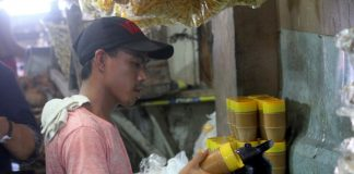 A trader makes the steam emitted from a kettle as softener of plastic material being used as seal of peanut butter containers at Bankerohan Public Market in Davao City on Tuesday. Lean Daval Jr.