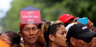 SPEAKING OUT LOUD. An elderly man wears a small placard on his head written with 'Lift Martial Law, Now' during a protest rally against the Duterte administration at the Freedom Park in Davao City a few hours before President Duterte delivers his second State of the Nation Address (SONA) on Monday. LEAN DAVAL JR.